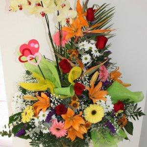 centro de flores variadas de colores con planta de orquídea