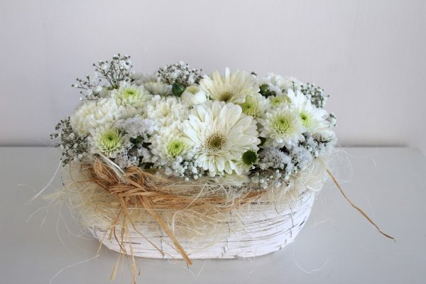 Cesta de mimbre con flores variadas de color blanco
