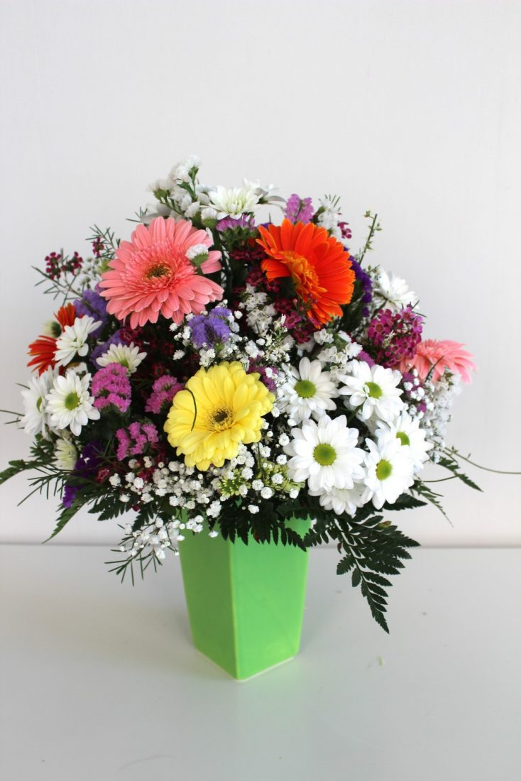Jarrón verde con flores variadas de colores