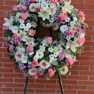 corona fúnebre de flores variadas con forma redonda