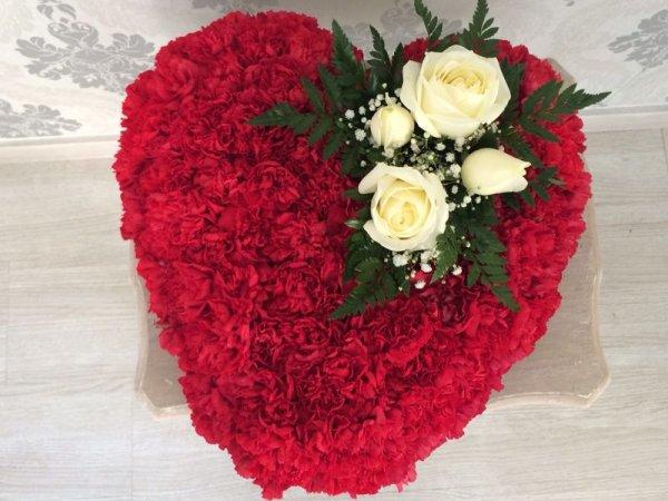 corazón rojo de claveles rojos con un detalle de rosas blancas
