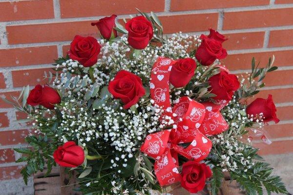 """capazo de rafia natural con 12 rosas rojas. En el capazo lleva el texto """"te amo"""" escrito"""