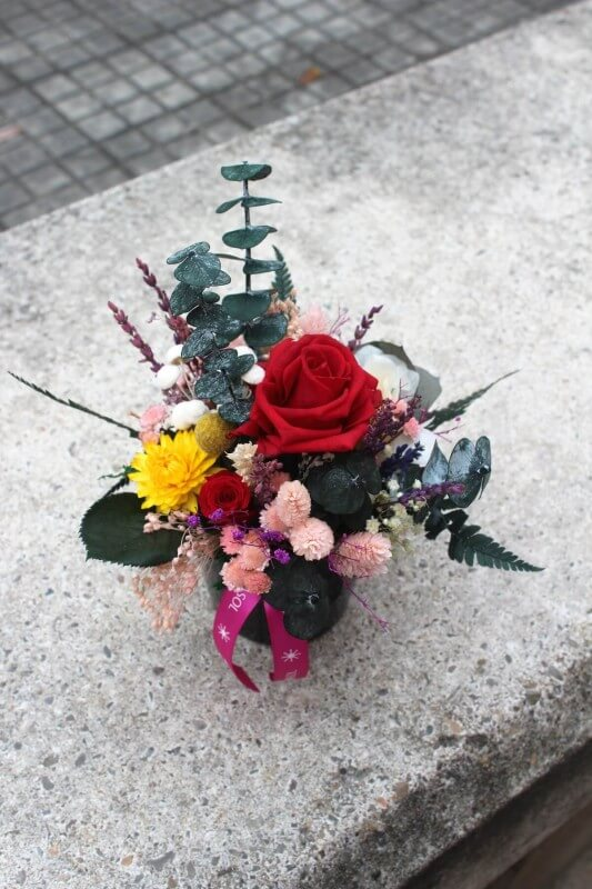 centro de flores de cerámica negra con flores preservadas