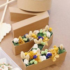 letra de cartón con flores preservadas en su interior