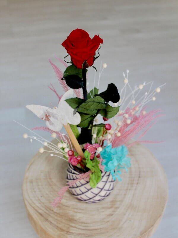 rosa eterna decorada con un jardín de flores preservadas y mariposa