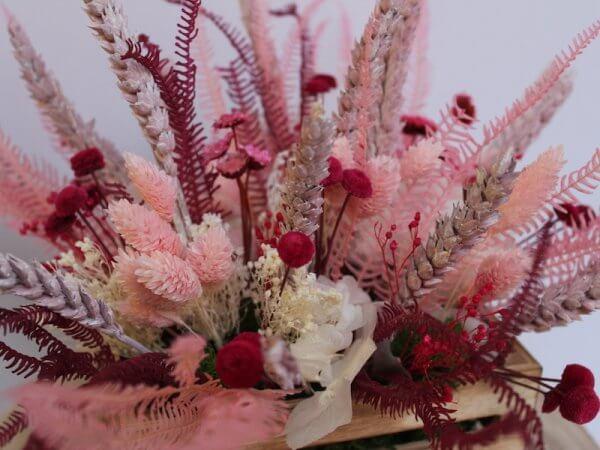 caja de madera con flor seca rosada y frambuesa