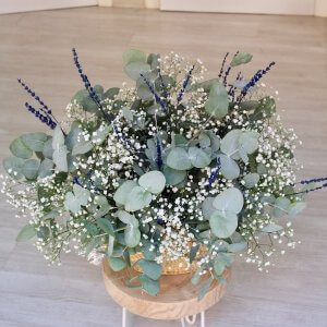 Cesto de rafia natural lleno de eucalipto natural con paniculata y lavanda preservada